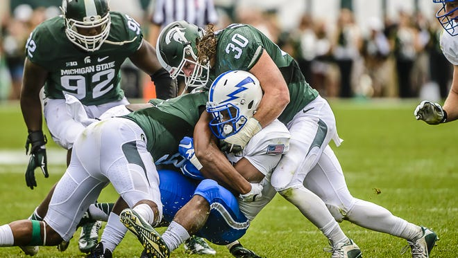 MSU's Montae Nicholson, left, and Riley Bullough, right, converge to bring down Air Force's Jacobi Owens Saturday at Spartan Stadium. MSU has  adopted rugby tackling techniques, using shoulder tackles with driving legs.