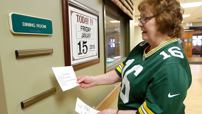 Marge Reim hangs up the days menus at the St Francis Home.