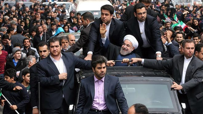 A handout picture made available by the presidential official website shows Iranian President Hassan Rowhani, center, greeting his supporters in the city of Rasht, northern Iran on April 15, 2015.