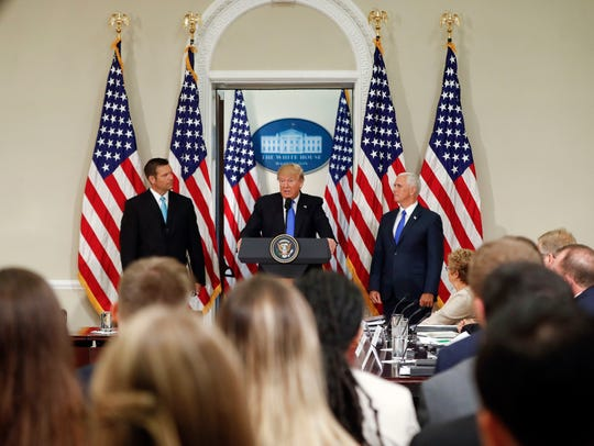 "In this July 19, 2017, file photo, President Donald Trump, with Kansas Secretary of State Kris Kobach (left) and Vice President Mike Pence (right), speaks at a meeting of the Presidential Advisory Commission on Election Integrity in the Eisenhower Executive Office Building on the White House complex in Washington. Trump's campaign to discredit the news media has spread to state and local officials, who are echoing his use of the term ""fake news"" as a weapon against unflattering stories and information that can tarnish their images."