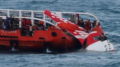 Indonesian search and rescue personnel pull wreckage