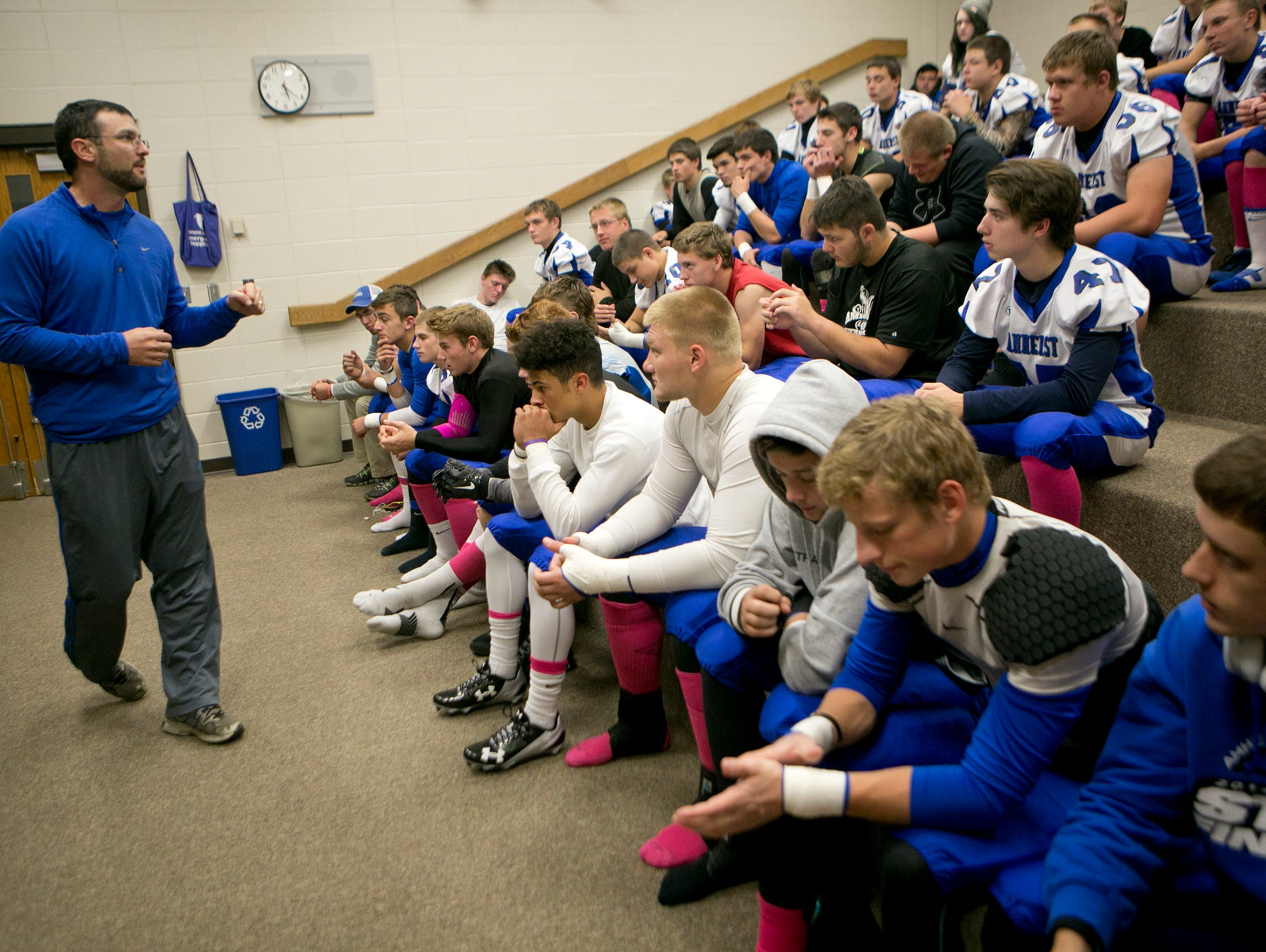 Amherst head coach Mark Lusic address the football