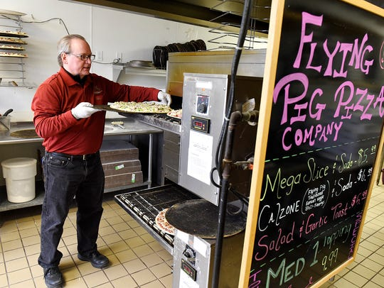 Roy Dodd, owner of Flying Pig Pizza, loads pizzas ordered