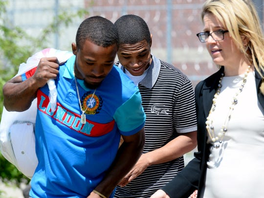 Davontae Sanford, 23, smiles as he walks out of  the Bellamy Creek Correctional Facility with his brother Deshon, left, and two of his lawyers Wednesday, June 8, 2016, after almost 10 years behind bars for a quadruple homicide officials now believe he did not commit. Professional hitman Vincent Smothers has said he, not Sanford, killed four people in a drug house in Detroit in 2007.