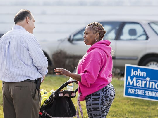 Republican Senate candidate John Marino talks with Shayalya Matthews as he canvasses a neighborhood near Newark earlier this month.