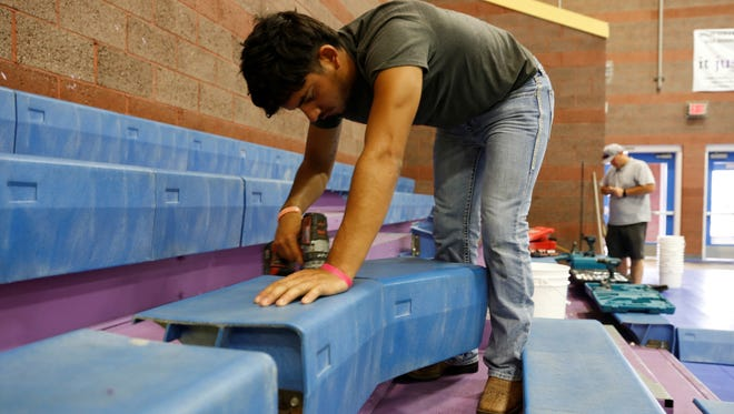 Marc Riddel of Aztec Well removes a bench from the bleachers in the Boys & Girls Clubs of Farmington gymnasium on Tuesday.