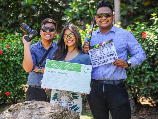 The management team of Project: Inspire display their Hafa Adai pledge card as they pose for a photo after the 600th pledge signing ceremony at the Valley of the Latte Adventure Park in Talofofo on Tuesday, March 15. From left: Director Justin Baldovino, Production Manager Erani Zuniga and Director Niel Romero.