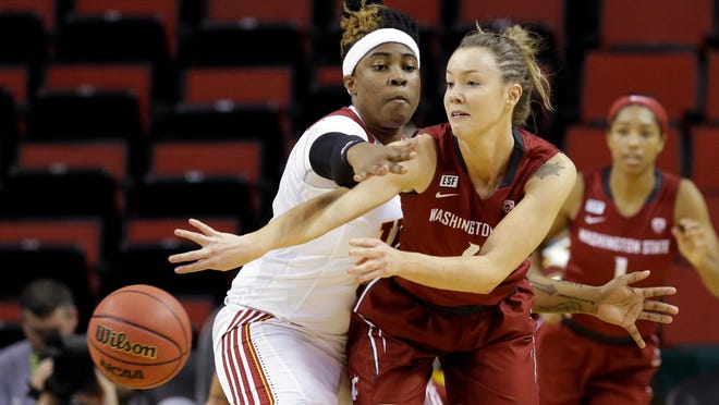 Washington State's Louise Brown, right, gets a pass off in front of USC's Kristen Simon during a game in March. Brown transferred to Tennessee, but is likely to miss the season after tearing an ACL.