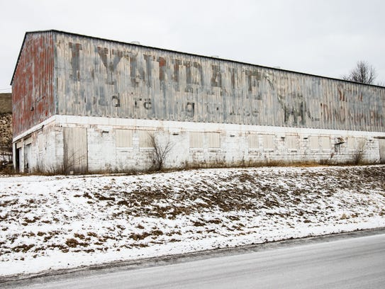 The paint on the side of an old white barn has chipped away revealing a decades-old sign advertising for the now-defunct Lynndale Race Track. The track operated for several years in the 1960s.