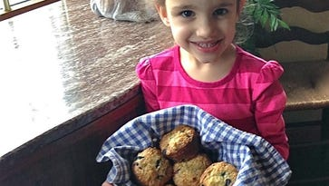 Emerson Heikenfeld shows off the banana blueberry muffins she helped create.