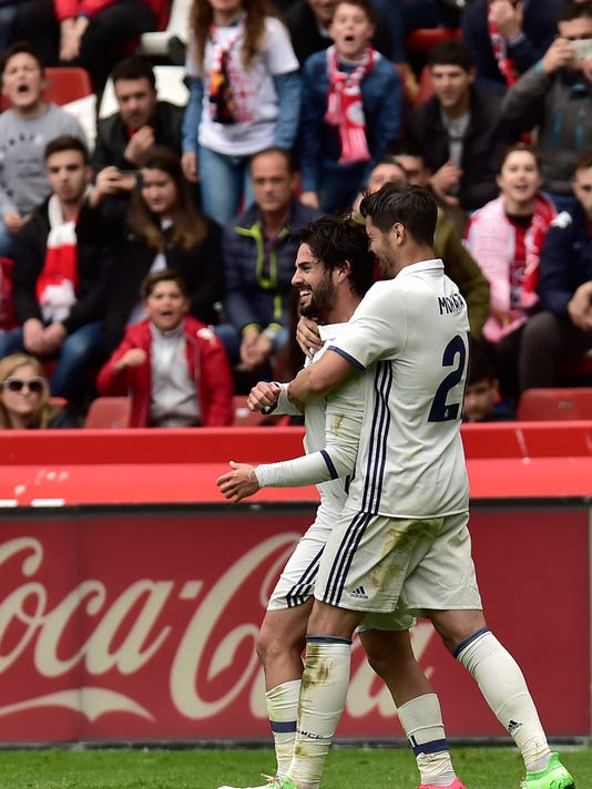 Real Madrid's Isco, left celebrates his goal with Alvaro Morata after scoring the third goal against Sporting de Gijon during the Spanish La Liga soccer match between Real Madrid and Sporting de Gijon, at El Molinon stadium in Gijon, northern Spain, Saturday, April 15, 2017. Real Madrid won the match 3-2. (AP Photo/Alvaro Barrientos)