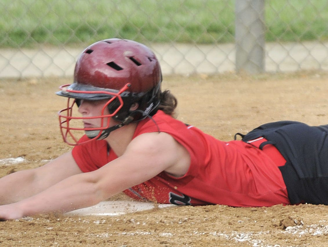 Taylor Cappella of Smyrna crosses home plate on a head-first slide to score a run for the Eagles.