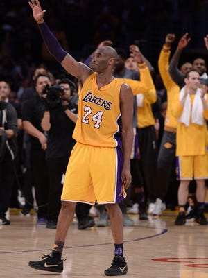 Los Angeles Lakers forward Kobe Bryant (24) waves to the Staples Center crowd as he leaves the game against the Utah Jazz in the closing seconds. Bryant scored 60 points in the final game of his career. Credit: Robert Hanashiro-USA TODAY Sports