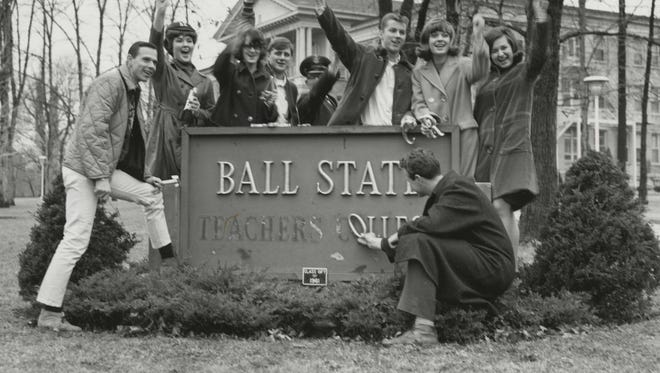 Ball State students are shown removing Teachers College from the sign in 1965 when it became Ball State University.