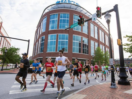 Delaware Marathon Running Festival participants make the turn from West Street to Justison Street in Wilmington.