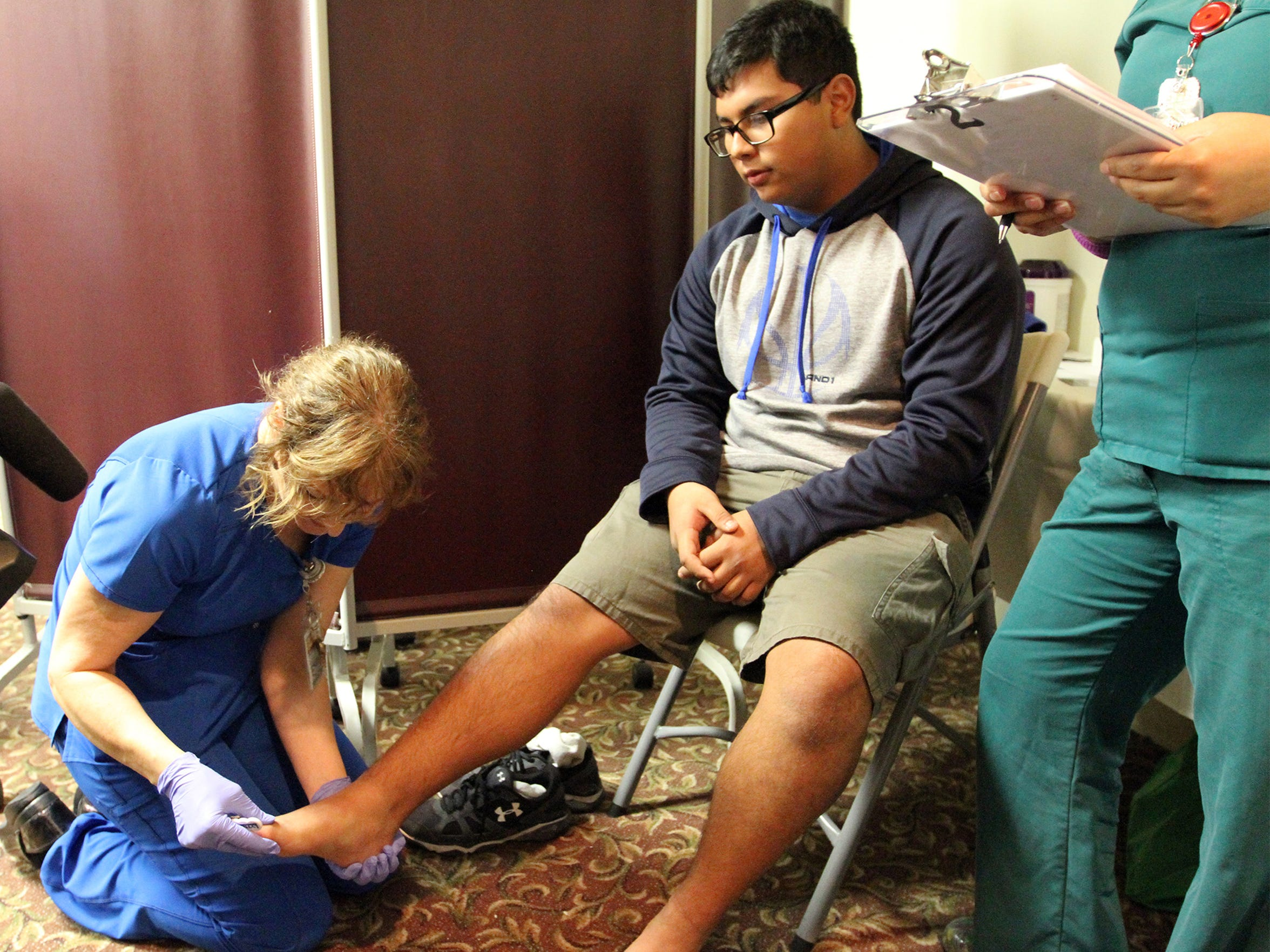 Edward Martinez, 19, of Brownsville gets his feet checked by registered nurse Heather Thiel, left, during his first diabetes screening during a free public health screening at Valley Baptist Hospital in Brownsville.