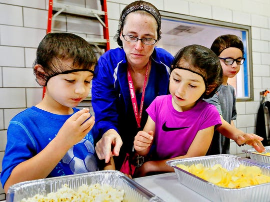 From left, Nathan Franck, 6, Heather Herr, Anissa Herr, 6, and Jackson Franck, 8, all of Hanover, sample popcorn and chips Wednesday, June 15, 2016, during a tour of Martin's Potato Chips during the 18th annual Made in America Tours Event, which runs June 15-18, at the factory in Thomasville. Dawn J. Sagert photo