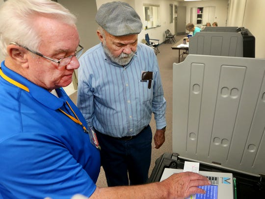 Poll worker Gary Evans, left, shows voter Larry Derryberry,