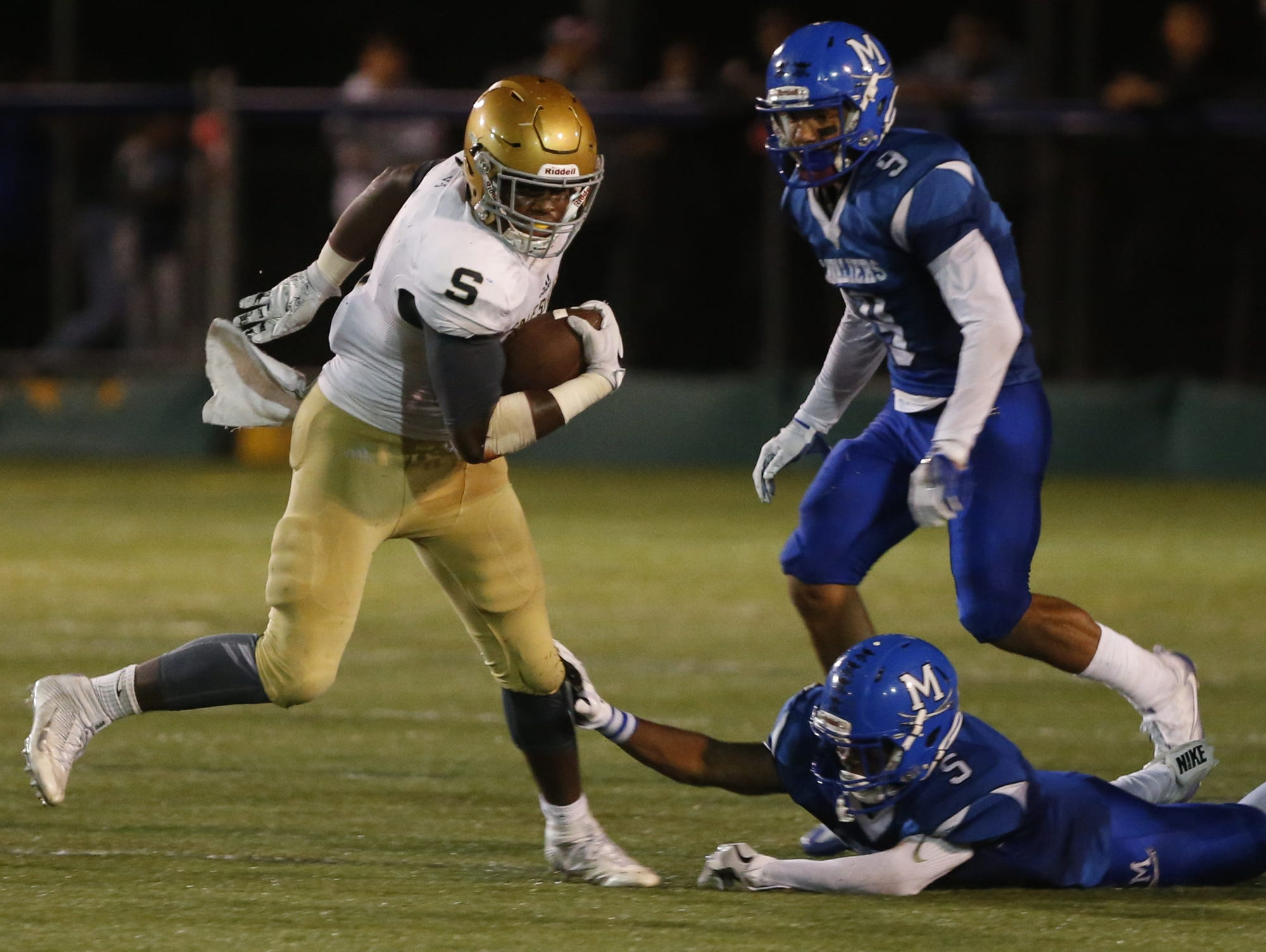 Salesianum's Josh Patrick gets away from Middletown's Shane Wilkins (9) and Ernest Washington on a long run in the second quarter at Cavalier Stadium Friday.
