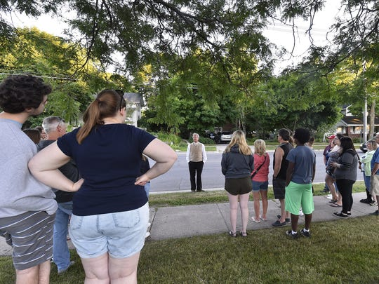 """The """"Murder & Mayhem Tour"""" makes a stop along South Michigan Street in Sturgeon Bay to hear from tour guide Stephan Reynolds, center, about the murders of former Door County Advocate owners Sumner and Grace Harris."""