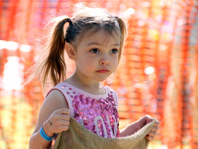 Rayna Winkler, 4, is ready for the next potato sack