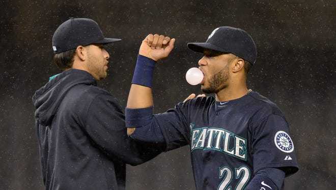 Seattle Mariners second baseman Robinson Cano, right, celebrates after the game against the New York Yankees at Yankee Stadium.