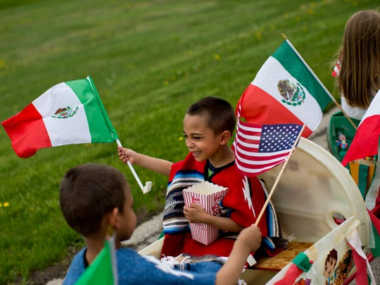 Jamarius Waldon, 6, of Port Huron, waves the flag of Mexico along with his twin brother Jamal during the Cinco de Mayo parade Saturday, May 9, 2015 in South Park in Port Huron.