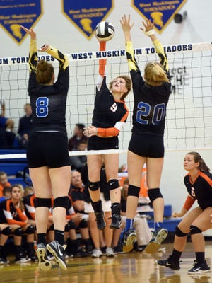 Abbey Kellish spikes the ball against West Muskingum's Delaney Mynes, left, and Hayley Barker during Ridgewood's 20-25, 25-22, 25-17, 25-21 win in a Division III sectional tournament gameon Tuesday at Gary Ankrum Gymnasium.
