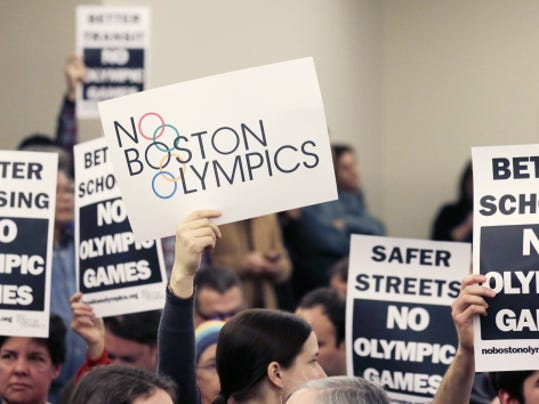 People hold up placards against the Olympic Games coming to Boston, during the first public forum Feb. 5 regarding the city's 2024 Olympic bid, in Boston.
