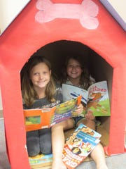 Best friends Brianna Thompson and Nola Lepage, both age 9, spent some time reading in the Campbellsport Public Library's dog house. Youth off all ages are en- courage to visit the library.