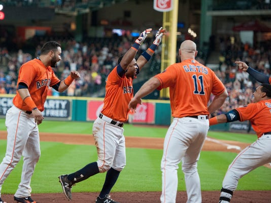 The Houston Astros Luis Valbuena, center, is greeted by teammates as he celebrates his walk-off home run against the Oakland Athletics in the ninth inning of a baseball game Friday, July 8, 2016, in Houston. (AP Photo/George Bridges)