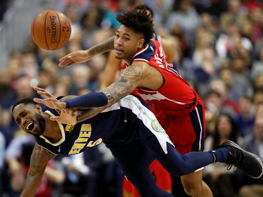 Washington Wizards forward Kelly Oubre Jr., right, fouls Denver Nuggets forward Will Barton (5) during the second half of an NBA basketball game Friday, March 23, 2018, in Washington. (AP Photo/Alex Brandon)