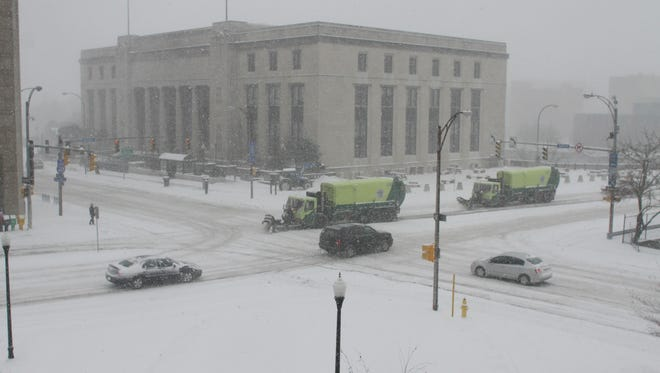 Plows make their way through downtown Rochester at Court Street and South Avenue.