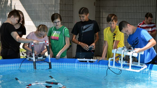 Camp participants test their remote-operated vehicles in a large outdoor swimming pool at the Wisconsin Maritime Museum.