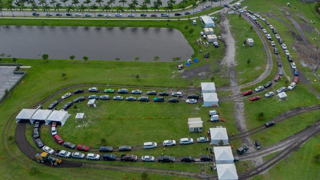 People wait in their cars to be tested for the coronavirus with drive-up rapid testing at the FITTEAM Ballpark of the Palm Beaches in West Palm Beach, Florida, on Oct. 23, 2020.