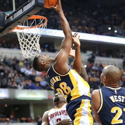 Pacers center Roy Hibbert looks for room to pass the bakll under the basket around Cleveland center Timofey Mozgov in the first half of the game at Bankers Life Fieldhouse on Friday, Feb. 27, 2015.
