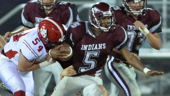 East Robertson running back,Tommy Blakemore (5)  is tackled by Jo Byrns' Jackson Jones (54) and John Dowlen (44).