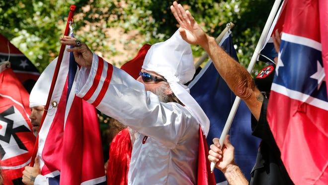 Klan members salute during a KKK rally in Charlottesville, Va. on July 8, 2017.