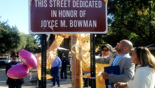 Shreveport City Councilman Jerry Bowman Jr. unveils a sign dedicating the 3600 block of Milton Street in honor of  the late Joyce M. Bowman, a former Shreveport City Councilwoman and Caddo Commissioner.