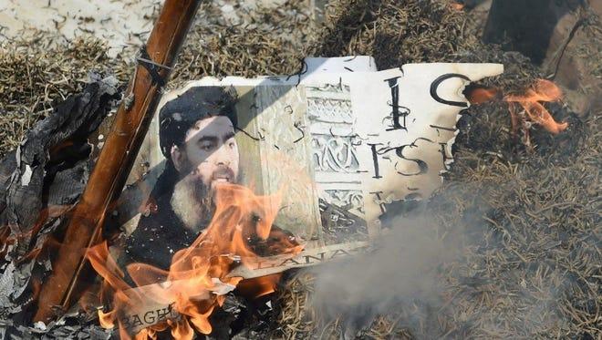 Indian Shiite Muslim demonstrators burn an effigy of the Islamic State group leader Abu Bakr al-Baghdadi during a protest in New Delhi on June 9.