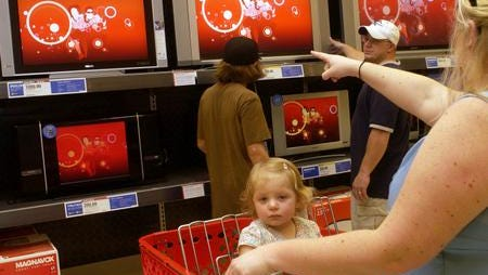 Lori Kerker points out HD television set to her husband Kevyn and son, K.C., 12, as  her daughter Alexis, 16 months, sits in a cart on Sunday, Jan. 7, 2007, at a Target store in Viera, Fla. There are many options to consider when shopping for an HDTV set.