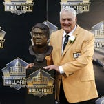 Former NFL player Mick Tingelhoff poses with his bust during inductions Saturday at the Pro Football Hall of Fame in Canton, Ohio.