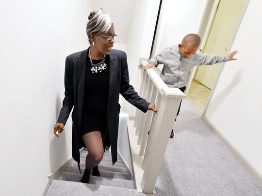 With her grandson Rashard, 6, leading the way, Maggie Miller climbs the stairs at her new home on East Locust Street on Friday. About a dozen family members, friends and co-workers came out for the surprise.