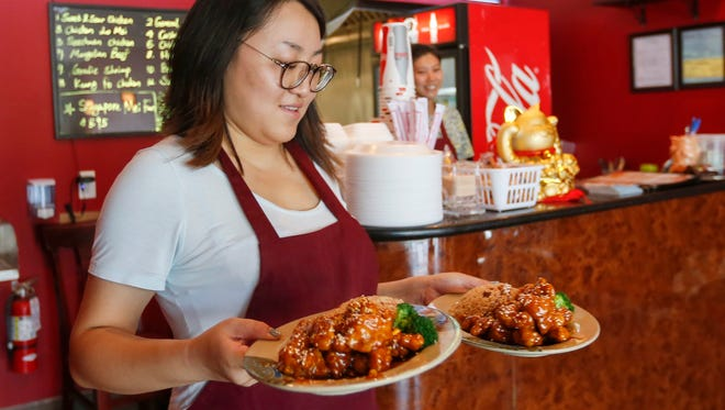 Tiffany Zhng brings out a lunch order at Asian Hut on Tuesday, August 16, 2016. The new restaurant is located at 1500 E. Sunshine St.