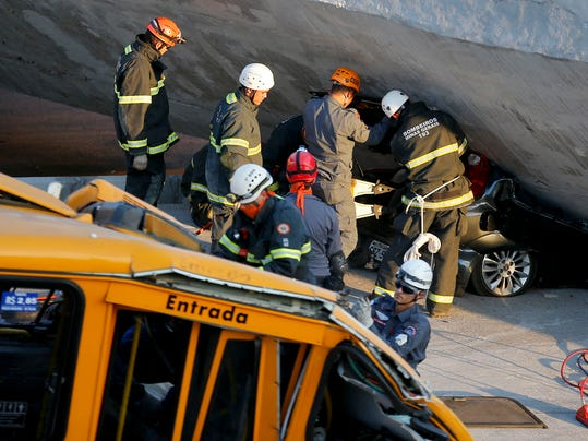 Fire department personnel work to retrieve a car from underneath a collapsed bridge in Belo Horizonte, Brazil, Thursday, July 3, 2014. The overpass under construction collapsed Thursday in the Brazilian World Cup host city. The incident took place on a main avenue, the expansion of which was part of the World Cup infrastructure plan but, like most urban mobility projects related to the Cup, was not finished on time for the event. (AP Photo/Victor R. Caivano)