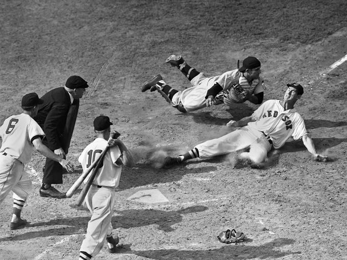 Yankees catcher Yogi Berra, the ball in his bare hand,