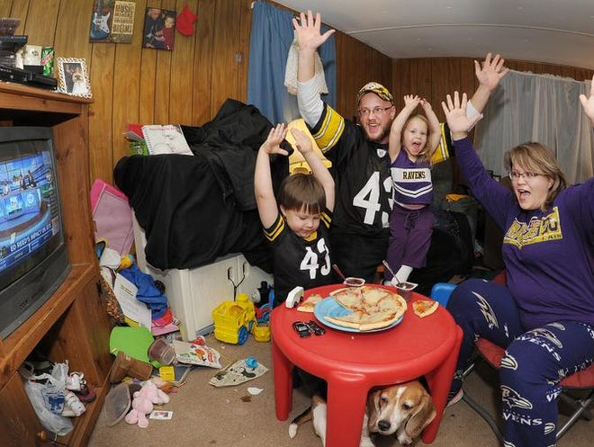 Jennifer and Ben Antonik with their kids Delaney and Dmitri watch the game at their home near Lincoln, Pa. The guys cheer Steelers; the gals cheer Ravens.
