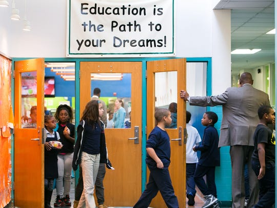Principal Jeffers Brown holds the door as students arrive for their lunch time while others leave after finishing their lunch at Stubbs Elementary School in Wilmington. A mystery donor paid $1,200 to cover the lunch bills for all students.