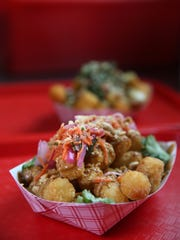 Peanut curry tots, front, served up with Old Bay tots