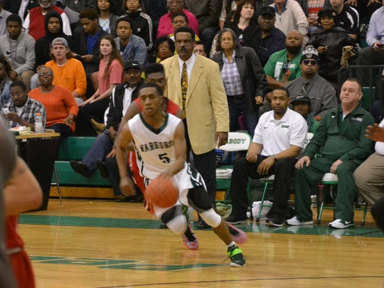 Peabody's Jacoby Ross (5) drives against Tioga during the 2015 Class 4A playoffs as his grandfather, Warhorses coach Charles Smith (center), and his uncle, Warhorse assistant Kedric Smith, look on.